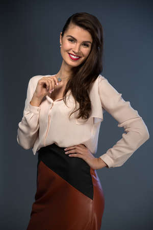 business style: Portrait glamorous brown-haired business style girl dressed in a blouse and a leather skirt