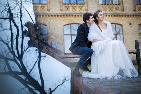 multiple exposure: Sposi abbracciando seduto su una panchina del parco. Imporre multipla effetto dell'esposizione. Archivio Fotografico