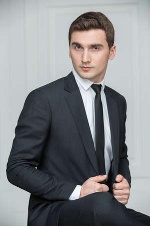Solid young man in black suit and tie. Studio portrait photography business. Zdjęcie Seryjne