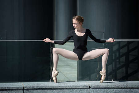 ballerina tights: Young graceful ballerina in black bathing suit on a background of the urban industrial landscape. Snapshot on the territory of modern stadium. Kiev. Stock Photo