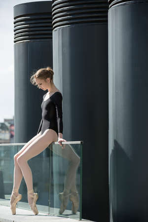 Young graceful ballerina in black bathing suit on a background of the urban industrial landscape. Snapshot on the territory of modern stadium. Kiev. Stock Photo