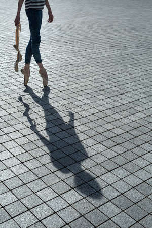 unleashed: Ballerina in blue jeans and pointe stands on tiptoe on a granite tile. In the hands of a couple of unleashed Poitiers. On the ground, the shadow of the beautiful dancer.