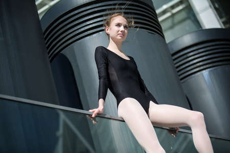 ballerina tights: Young graceful ballerina in black bathing suit on a background of the urban industrial landscape. Shooting with angle appear below. Snapshot on the territory of modern stadium. Kiev. Stock Photo