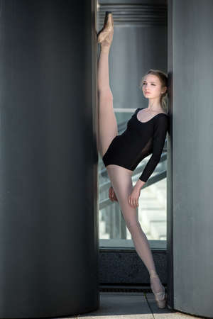 Young graceful ballerina in black bathing suit on a background of the urban industrial landscape. Model leg lifted high in the splits between the columns. Snapshot on the territory of modern stadium. Kiev.