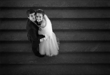 happy wedding: Couple in love is embracing on the stairs and looks up with a smile. Black and white photo.