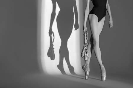ballerina girl: Cropping portrait of the legs graceful ballerina in a studio  on a white background. Dancer in a blue bathing suit is holding his pointe. Against the background of her beautiful shadow. Black and white photo. Stock Photo