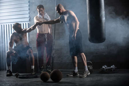 boy  naked: Rest three guys who have completed a complex crossfit workout in the gym.