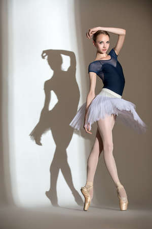 shadows: Portrait in full growth graceful ballerina in a studio on a white background. Dancer in a blue bathing suit and white tutu. Against the background of her beautiful shadow.