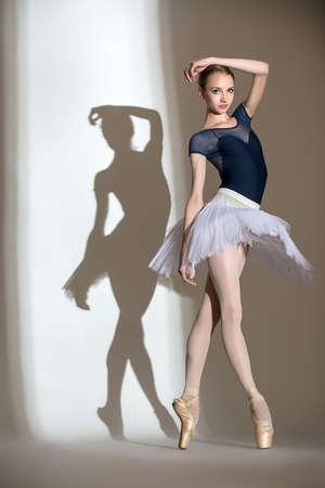 pies bailando: Retrato en pleno crecimiento de la bailarina agraciado en un estudio sobre un fondo blanco. Bailarina en un traje de baño azul y tutú blanco. En el contexto de su hermosa sombra. Foto de archivo