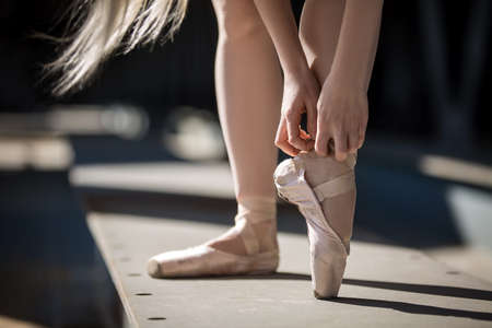 ballerina: Legs ballerina closeup. Dancer tying pointe shoes.
