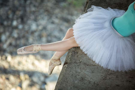 Ballerina sitting on the edge of the bridge. Feet shod with pointe. Dancer wearing a white tutu and blue swimsuit.