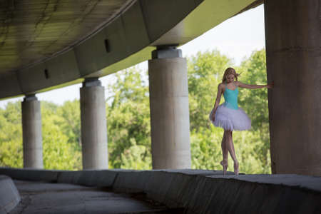 Graceful ballerina doing dance exercises on a concrete bridge against the backdrop of the prospects of support columns