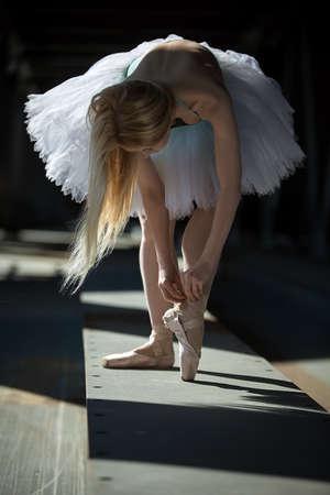Legs ballerina closeup. Dancer tying pointe shoes.