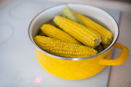 hob: Freshly corn in the yellow pot on a white hob Stock Photo