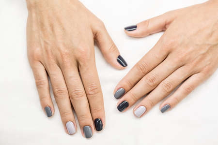 red nail colour: Beautiful manicure on hands of the girl. Stylish multicolored gray paint of different shades of gray on every finger.