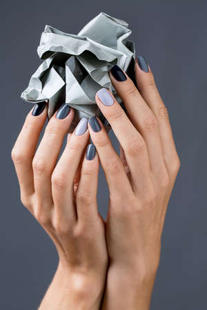 Stylish manicure in shades of gray female elegant handles. Hands holding a crumpled piece of gray textured paper.