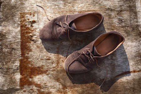 grunge wood: Old stylish shoes on a rusty brown color wooden board.