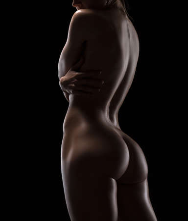naked woman back: Art nude picture of naked blonde in the studio. The lighting in the style of low-key. Stock Photo