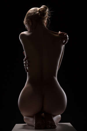 nude black woman: Art nude picture of naked blonde in the studio. The lighting in the style of low-key. Stock Photo