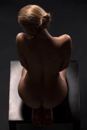erotic women: Art nude picture of naked blonde in the studio. The lighting in the style of low-key. Stock Photo