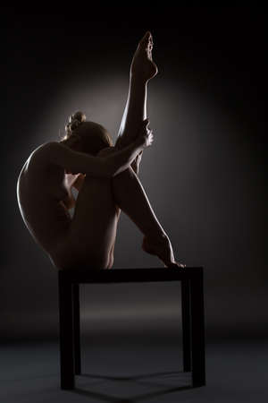 naked young people: Art nude picture of naked blonde in the studio. The lighting in the style of low-key. Stock Photo