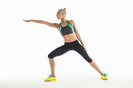 lunges: Rhythmic gymnast in a beautiful sportswear doing exercise in studio. Sportswoman standing lunges forward hand. Stock Photo