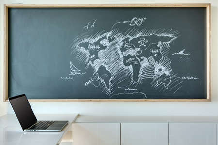 Board for drawing with chalk, which is painted white chalk map of the world in a humorous style. Blackboard is a minimalist interior. On the table is next to an open laptop with a blank screen. Stock Photo