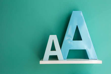 Letters A small and big size turquoise color on a white shelf. Shelf installed on a wall in a horizontal position. Fragment of interior decor.