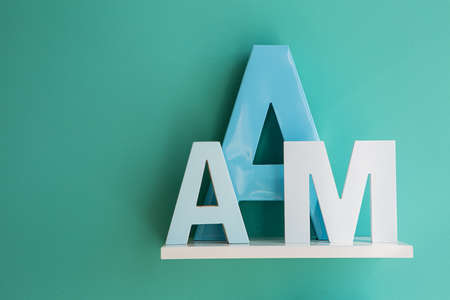 horizontal position: Letters A small and big size turquoise color and letter M on a white shelf. Shelf installed on a wall in a horizontal position. Fragment of interior decor.