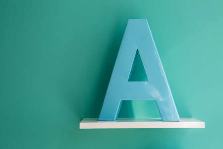 horizontal position: Letter A turquoise color on a white shelf. Shelf installed on a wall in a horizontal position. Fragment of interior decor.