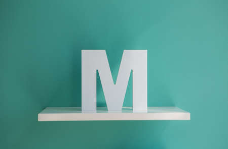 decorative letter: Letter M turquoise color on a white shelf. Shelf installed on a wall in a horizontal position. Fragment of interior decor.