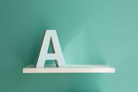 horizontal position: Letter A white color on a white shelf. Shelf installed on a wall in a horizontal position. Fragment of interior decor. Stock Photo