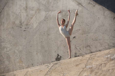 ballerina costume: Slim dancer stands in a ballet pose on a gray urban concrete background. Outdoors shooting with sun light. Stock Photo