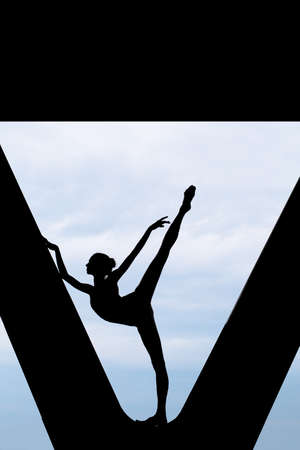 choreographic: Silhouette of a graceful ballerina in a black bathing suit that makes choreographic exercise in imaginative in support of the bridge against the backdrop of an overcast sky. Stock Photo