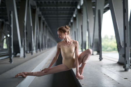 leotard: Full-length portrait of young and graceful ballerina in a flesh-colored bathing suit, which is in hareografichnoy pose, amid the urban landscape of the bridge. Stock Photo