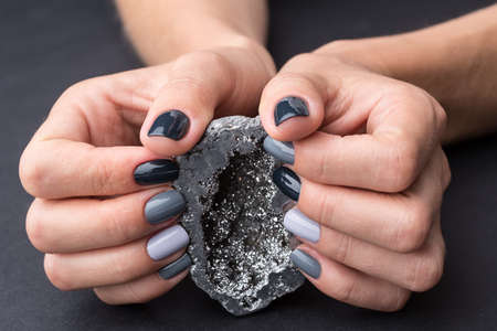 tonality: Well-groomed female hands with a stylish manicure holding a beautiful textured silver mineral. Nail painted gray paint different tonality. Grey neutral background.
