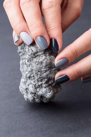 tonalit�: Soign� mains des femmes avec une manucure �l�gante tenant une belle min�rale argent textur�. Nail peint peinture grise tonalit� diff�rente. Fond neutre Grey. Banque d'images