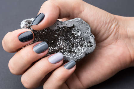 tonality: Well-groomed female hand with a stylish manicure holding a beautiful textured silver mineral. Nail painted gray paint different tonality. Grey neutral background.