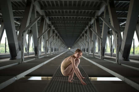 full height: Portrait full height of young and graceful ballerina in a flesh-colored bathing suit, amid the urban landscape of the bridge.