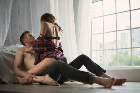 sexo pareja joven: Besos apasionados pareja, ni�o y ni�a sentada en el piso de madera cerca de la cama revuelta frente a la ventana. Foto de archivo