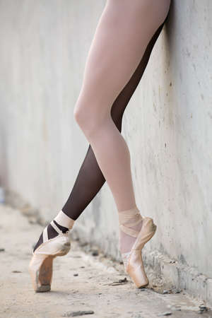 ballerina tights: Photo of the young graceful ballerina feet close-up on a background of textured concrete wall. Legs dressed in different colored tights black and white.