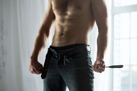 Cropped hands of topless guy with jeans unbuttoned playfully holding a whip BDSM. The picture in the studio on a background window.