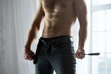 seins nus: Mains de rognage des gars torse nu avec un jean déboutonné tenant un fouet ludique BDSM. L'image dans le studio sur une fenêtre de fond. Banque d'images