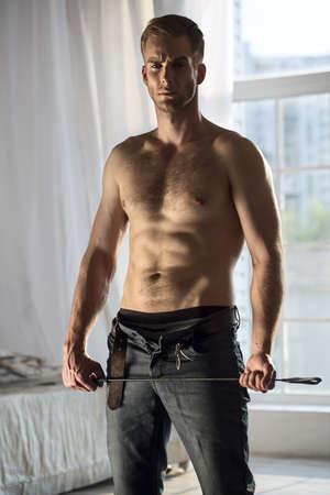 seins nus: Beau mec torse nu avec un jean déboutonné tenant un fouet ludique BDSM. L'image dans le studio sur une fenêtre de fond.