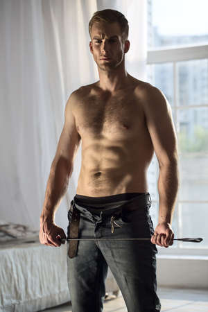 cuerpos desnudos: En topless hombre hermoso con los pantalones vaqueros se desabroch� la celebraci�n juguetonamente un l�tigo BDSM. La imagen en el estudio en un fondo de la ventana.