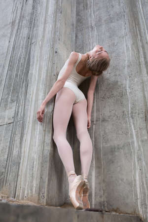 ballerina tights: Slender ballerina on a background of the concrete pillars of the industrial bridge. The girl gracefully posing static in dance poses.