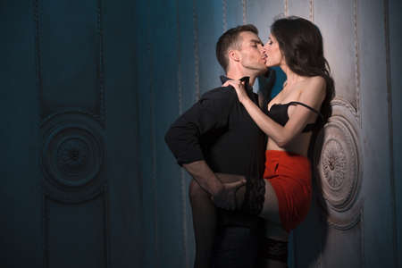 adult sex: Couple kissing passionately. Man Woman pinned against the wall and pulled her to her leg. A girl in a short red skirt and stockings. Stock Photo