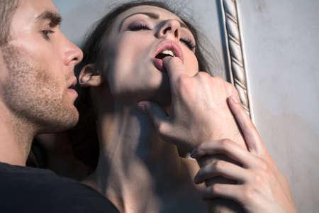 sexo: Dos amantes bajo la pared de un hermoso interior. Ella chupa un socio dedo, sosteniendo su mano, primer plano.