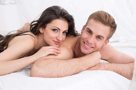 sexuel: Bonne jeune couple allong� dans son lit blanc, en regardant la cam�ra. Fille embrassant gars. Lumi�re du matin.