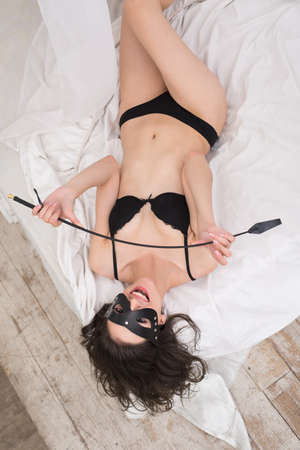 bdsm: Playful brunette in black leather mask and black underwear lying on white sheet in a bed and holding a whip for BDSM. Stock Photo